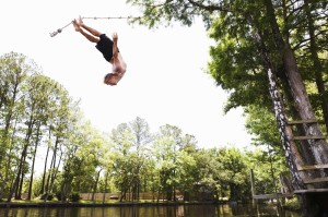 A teenage boy swinging from a rope swing into a lake.